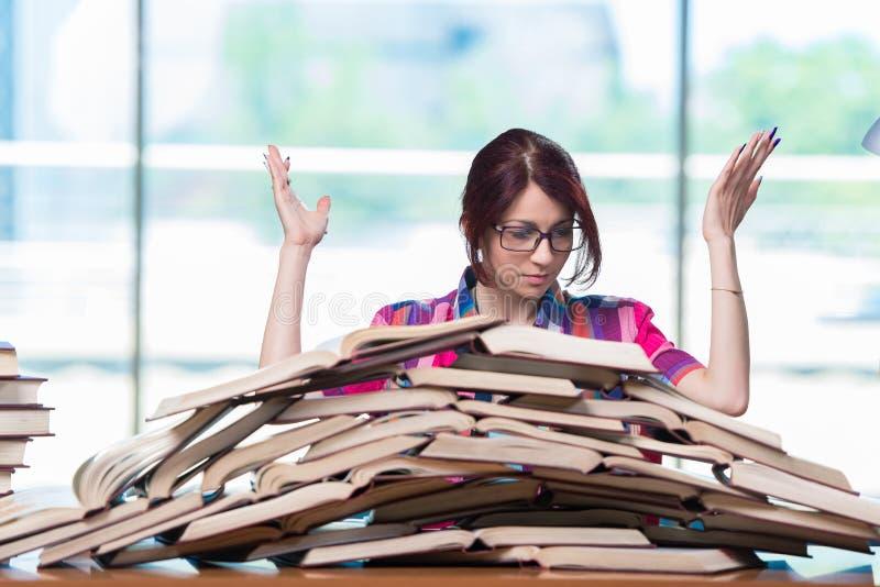 De jonge vrouwelijke student die voor examens voorbereidingen treffen royalty-vrije stock afbeelding