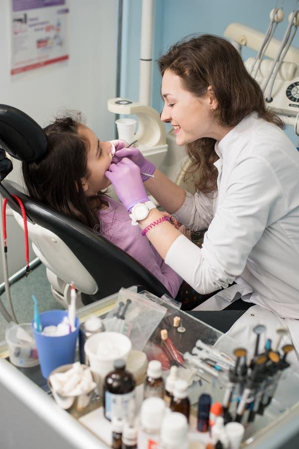 De jonge vrouwelijke tandarts behandelt geduldige meisjestanden op tandkantoor Tand apparatuur stock afbeelding