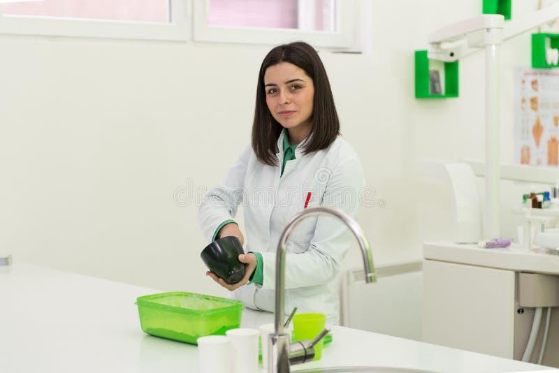 De jonge Vrouwelijke Vorm van Tandartsworking on the royalty-vrije stock foto