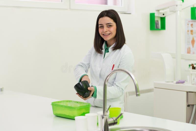De jonge Vrouwelijke Vorm van Tandartsworking on the stock foto's