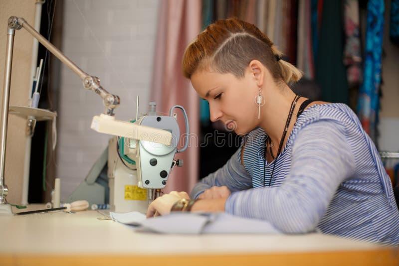 De jonge vrouwelijke werken van de blondenaaister aangaande naaimachine kledings verwerkende industrie royalty-vrije stock afbeelding