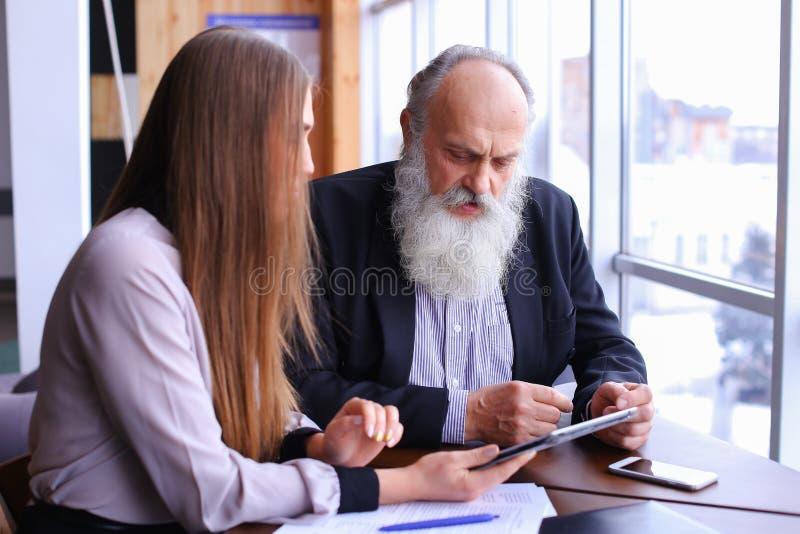 De jonge vrouwelijke werkgever debatteert de oude werknemer problemen in zaken bespreekt stock afbeeldingen