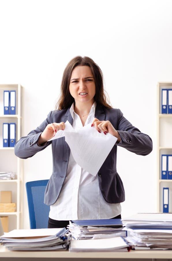De jonge vrouwelijke werknemer ongelukkig met het bovenmatige werk royalty-vrije stock afbeeldingen