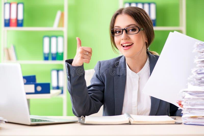 De jonge vrouwelijke werknemer zeer bezig met aan de gang zijnde administratie stock afbeelding