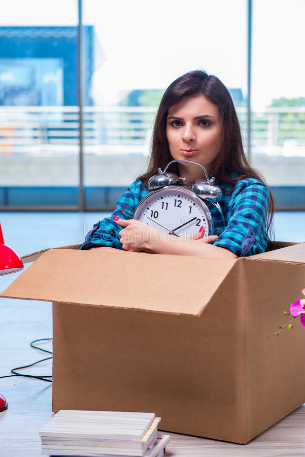 De jonge vrouwen bewegende persoonlijke bezittingen stock afbeelding