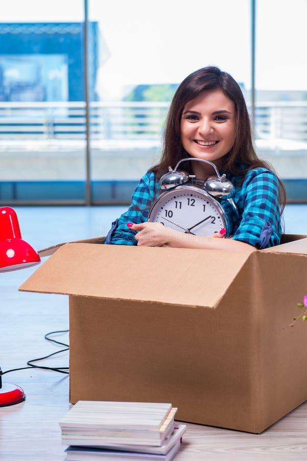 De jonge vrouwen bewegende persoonlijke bezittingen stock foto's
