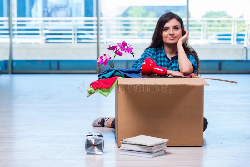 De jonge vrouwen bewegende persoonlijke bezittingen stock fotografie