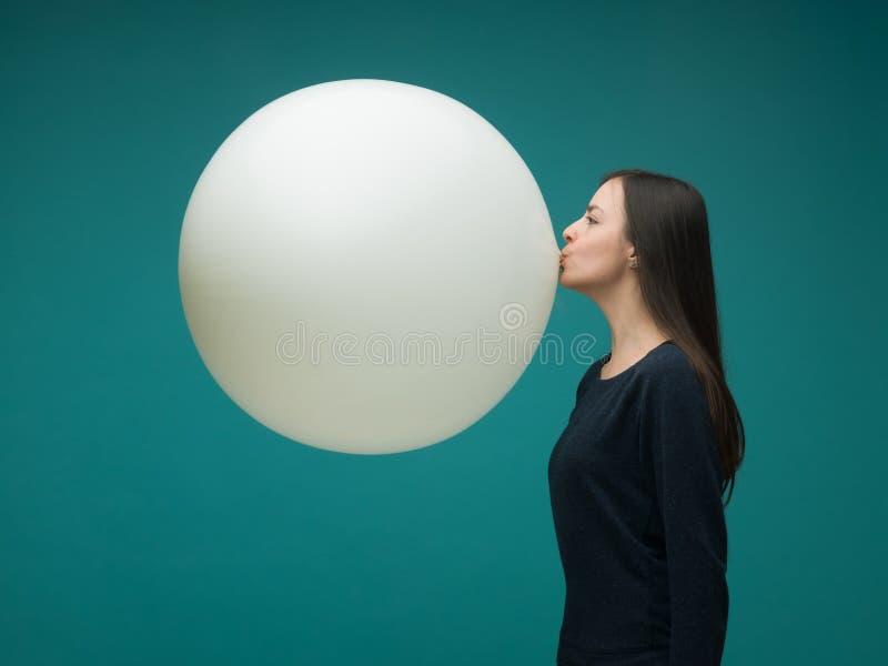 de jonge vrouwen blazen een ballon op stock fotografie