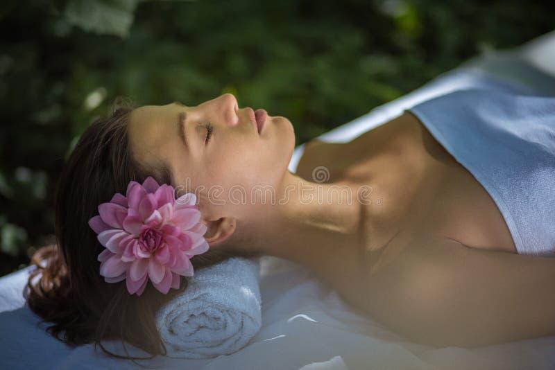 De jonge vrouwen die bij massagebed bij aard liggen, sluiten omhoog stock afbeeldingen