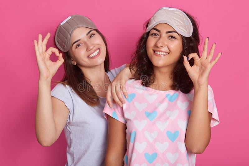 De jonge vrouwen die pyjama's en slaap dragen maskeert stellen geïsoleerd over roze achtergrond, die o.k. teken met hun vingers t stock fotografie