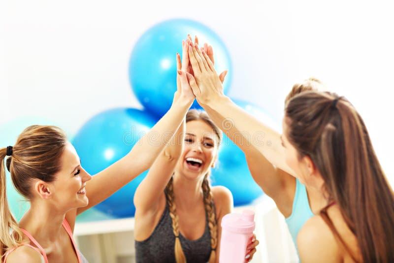 De jonge vrouwen groeperen gicing hoogte vijf bij de gymnastiek na training royalty-vrije stock afbeeldingen