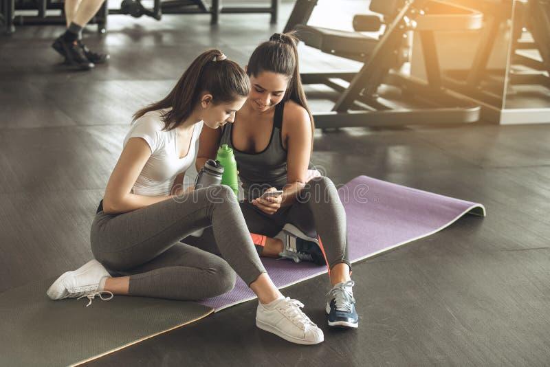 De jonge vrouwen oefenen samen in de gymnastiek uit stock foto's