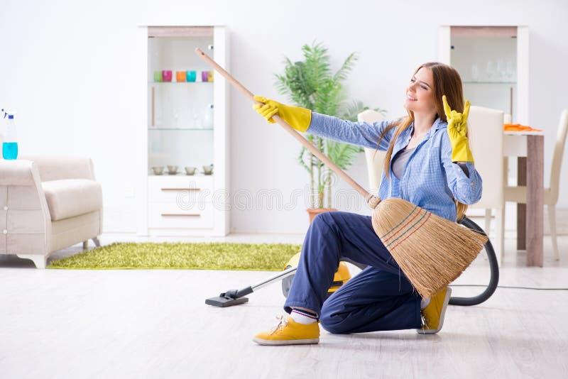 De jonge vrouwen schoonmakende vloer die thuis karweien doen royalty-vrije stock foto's