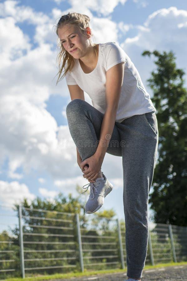 De jonge vrouwenagent houdt haar sporten verwond been stock foto's