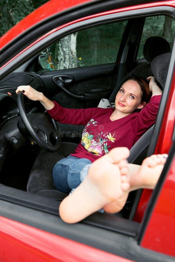 De jonge vrouwenbestuurder die in een rode auto rusten, zette haar voeten op het autoraam, gelukkig reisconcept royalty-vrije stock foto