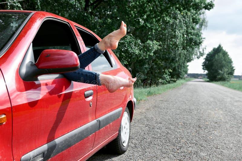 De jonge vrouwenbestuurder die in een rode auto rusten, zette haar voeten op het autoraam, gelukkig reisconcept royalty-vrije stock afbeelding