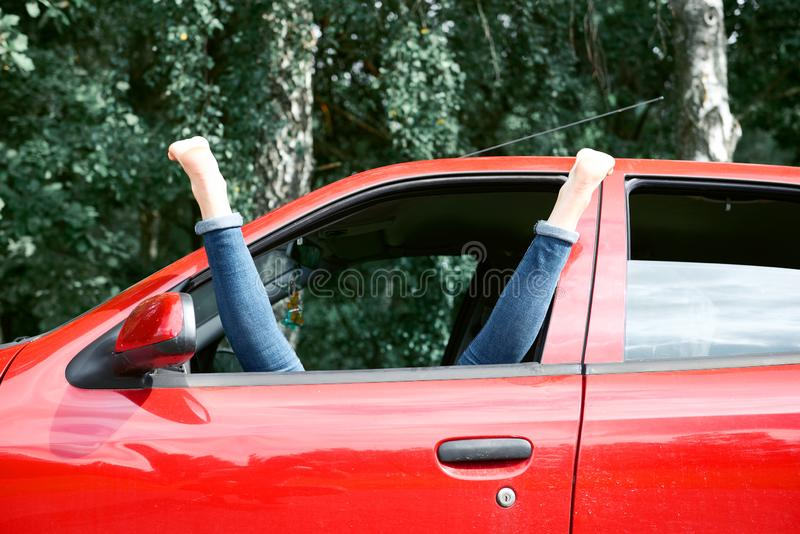De jonge vrouwenbestuurder die in een rode auto rusten, zette haar voeten op het autoraam, gelukkig reisconcept stock foto's