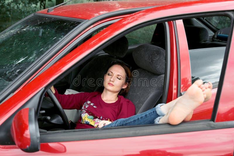 De jonge vrouwenbestuurder die in een rode auto rusten, zette haar voeten op het autoraam, gelukkig reisconcept stock afbeelding