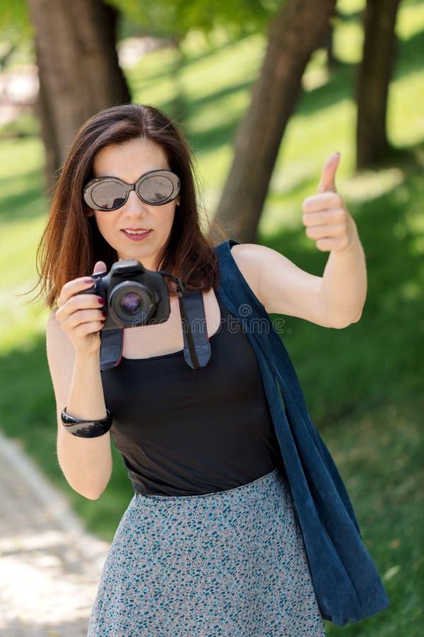 De jonge vrouwenfotograaf, toerist houdt een camera en toont t royalty-vrije stock fotografie