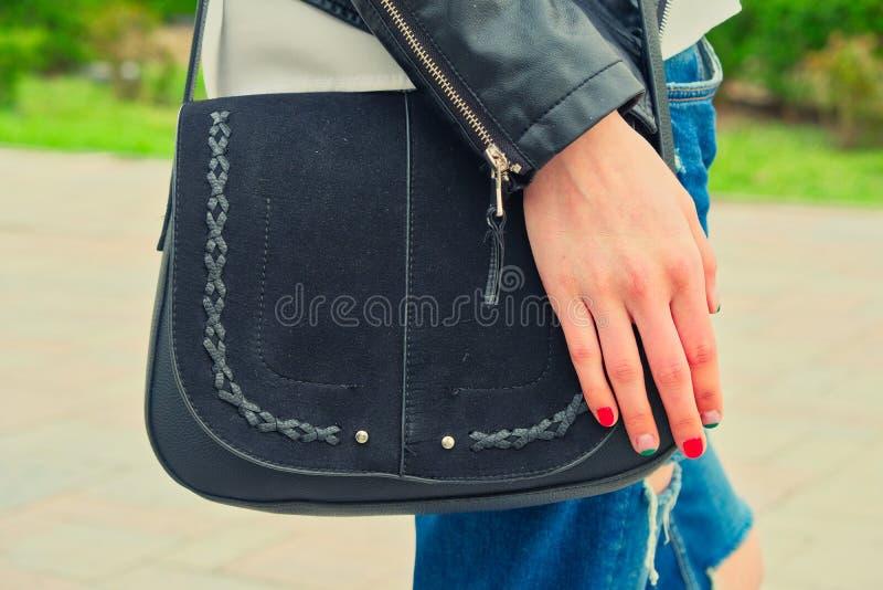 De jonge vrouwengreep yoyr overhandigt de zwarte handtas bij haar schouder het dragen riped jeans stock fotografie