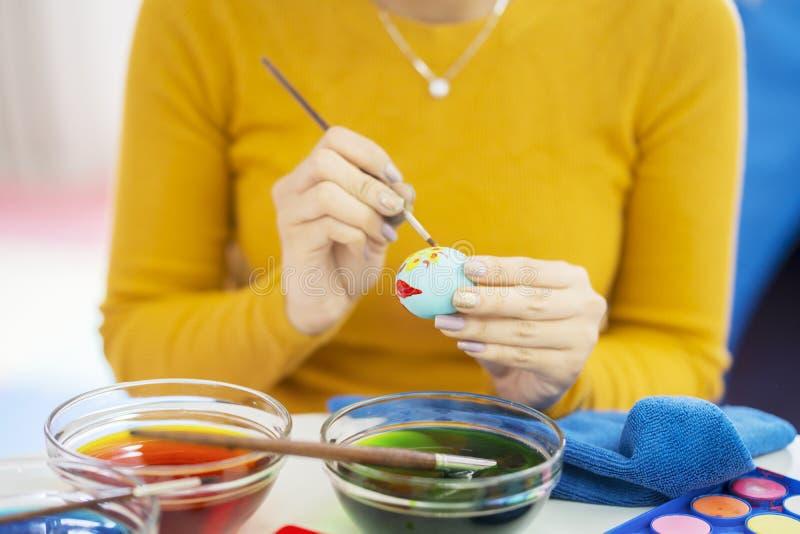 De jonge vrouwenhanden verfraait eieren met kleurstof royalty-vrije stock fotografie