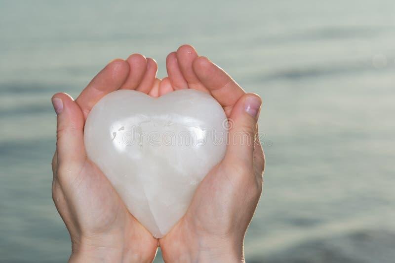 De jonge vrouwenholding poetste Hart van het room het wit gesneden Onyx in haar handen bij de zonsopgang voor het meer op Romaans royalty-vrije stock foto's