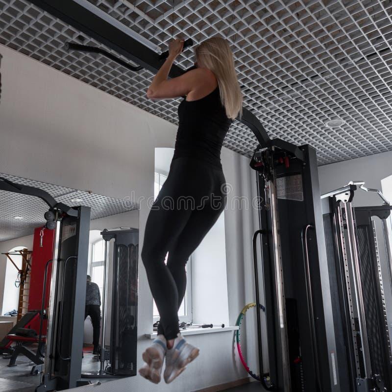 De jonge vrouweninstructeur in zwarte kleren met een mooi lichaam trekt op een metaalsimulator uit in de gymnastiek Meisje in bin royalty-vrije stock fotografie
