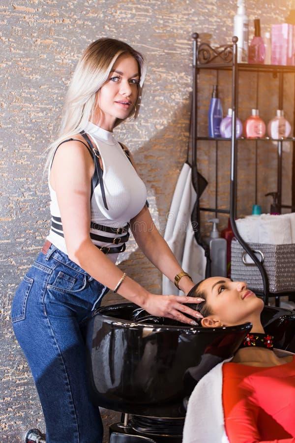 De jonge vrouwenkapper, kapper wast het haar van de cliënt Kuuroord stock afbeelding