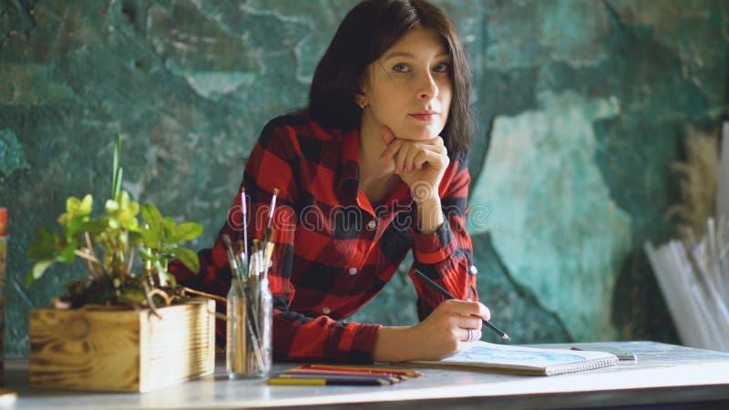 De jonge vrouwenkunstenaar het schilderen schets op document notitieboekje met potlood en onderzoekt camera royalty-vrije stock afbeelding