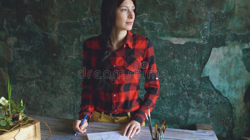 De jonge vrouwenkunstenaar het schilderen schets op document notitieboekje met potlood kijkt in venster royalty-vrije stock fotografie