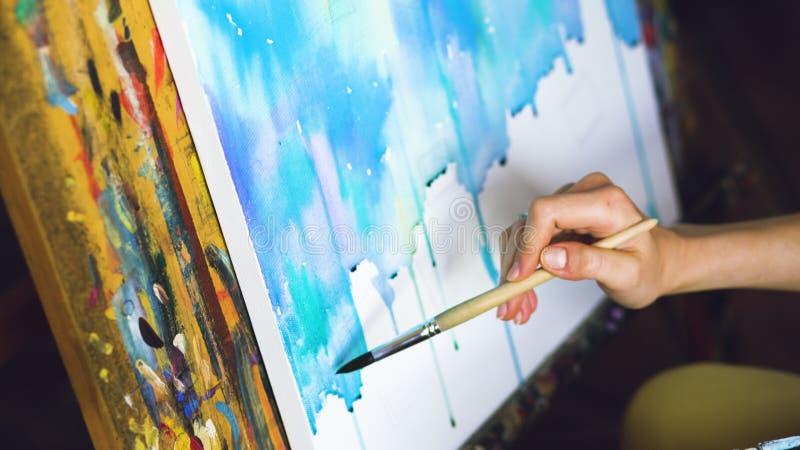 De jonge vrouwenkunstenaar trekt pictrure met waterverfverven en borstel op de close-uphand van het schildersezelcanvas stock afbeeldingen