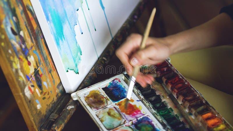 De jonge vrouwenkunstenaar trekt pictrure met waterverfverven en borstel op de close-uphand van het schildersezelcanvas royalty-vrije stock foto