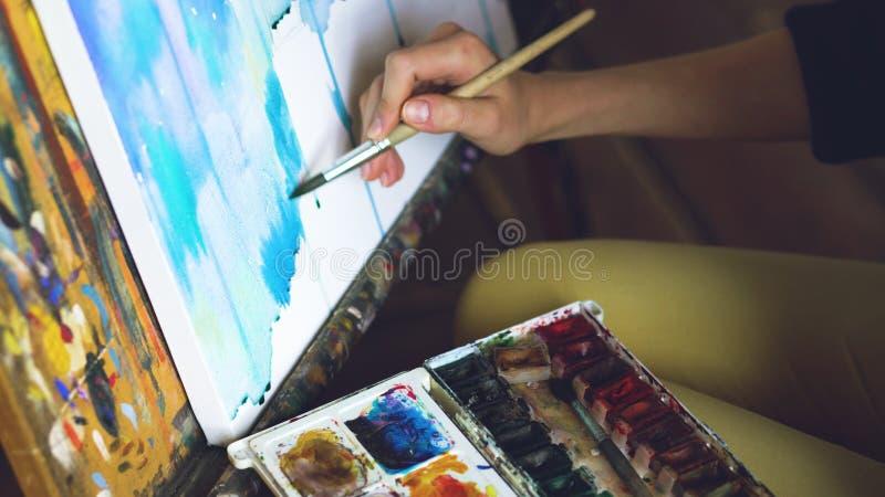De jonge vrouwenkunstenaar trekt pictrure met waterverfverven en borstel op de close-uphand van het schildersezelcanvas stock fotografie