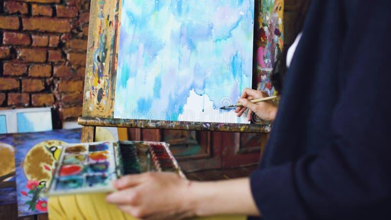 De jonge vrouwenkunstenaar trekt pictrure met waterverfverven en borstel op schildersezelcanvas stock foto