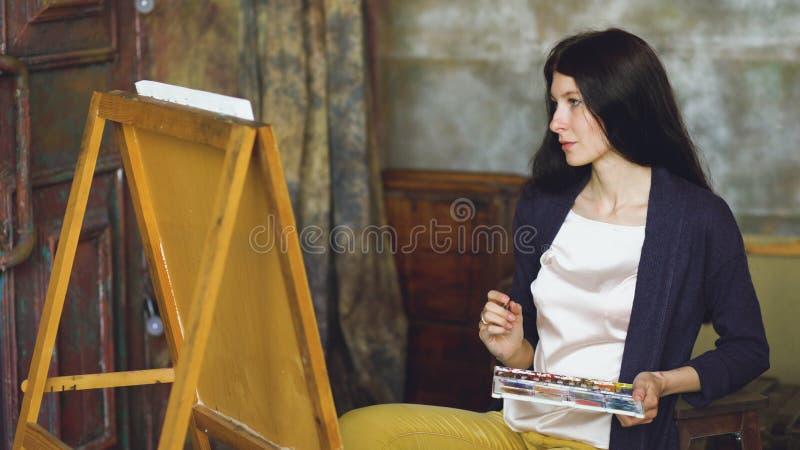De jonge vrouwenkunstenaar trekt pictrure met waterverfverven en borstel op schildersezelcanvas royalty-vrije stock foto