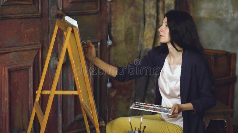 De jonge vrouwenkunstenaar trekt pictrure met waterverfverven en borstel op schildersezelcanvas royalty-vrije stock afbeeldingen