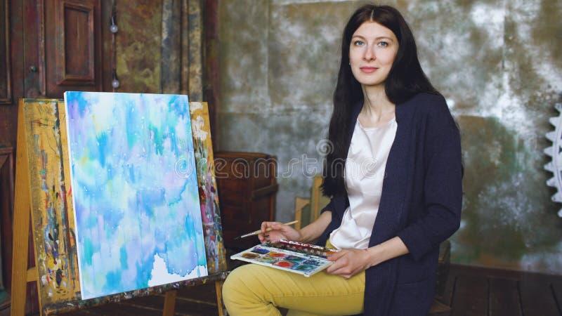 De jonge vrouwenkunstenaar trekt pictrure met waterverfverven en glimlach onderzoekend camera royalty-vrije stock afbeeldingen
