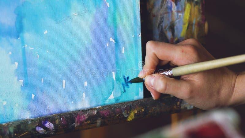 De jonge vrouwenkunstenaar trekt pictrure met waterverfverven en schrijft haar handtekening op afwerkingsclose-up stock foto