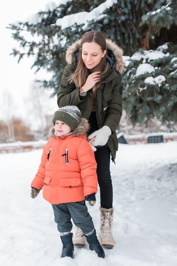 De jonge vrouwenmoeder, in de winter op straat, loopt met jonge zoon een jongen van 3 jaar De warme kleding van de jasjewinter Ru stock afbeelding