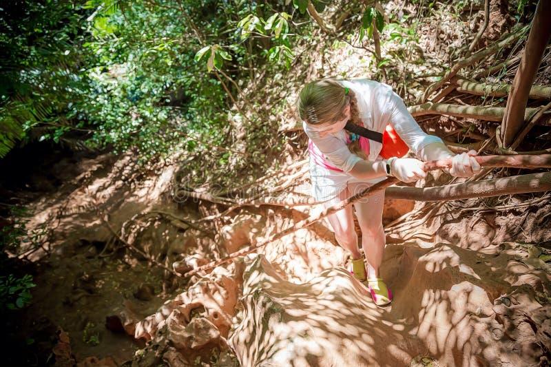 De jonge vrouwenreiziger in wit beklimt de berg op een kabel Mening van hierboven Tropische wildernis stock foto's