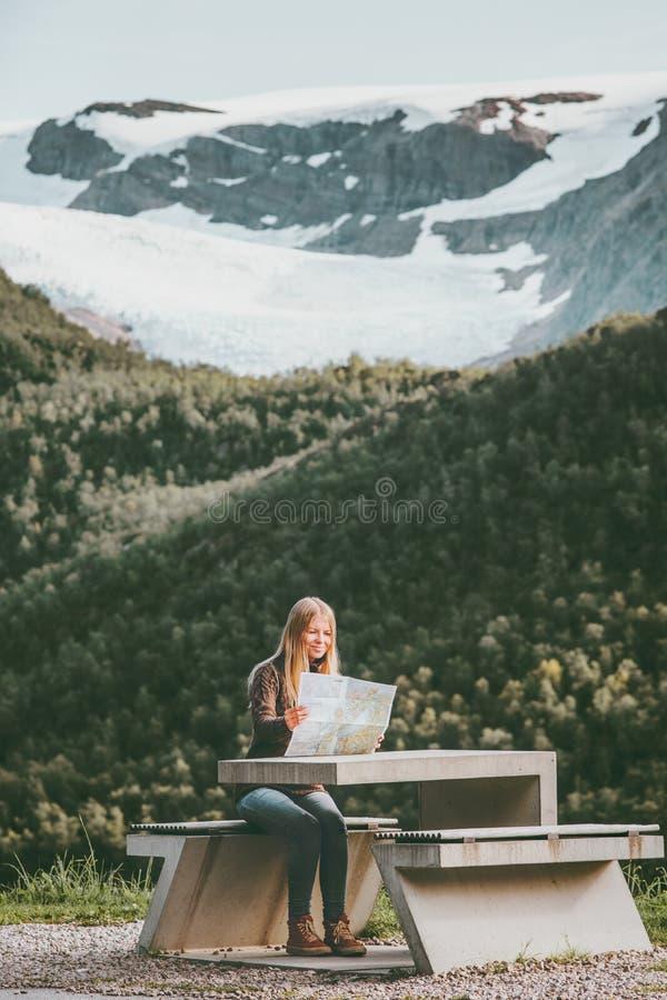 De jonge Vrouwentoerist met kaart de reis van de planningsroute in de zitting van Noorwegen bij de van het de Levensstijlconcept  royalty-vrije stock foto's