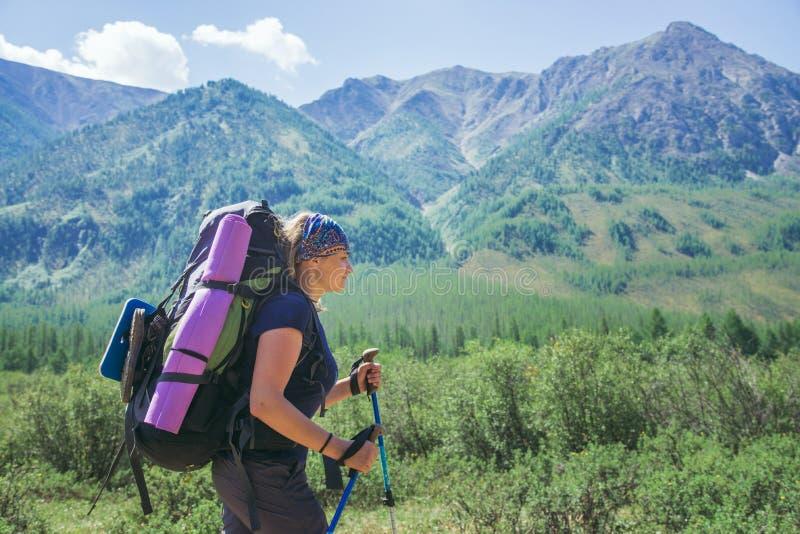 De jonge vrouwenwandelaar met rugzak en trekkingspolen op een zonnige dag op berg sleept stock foto