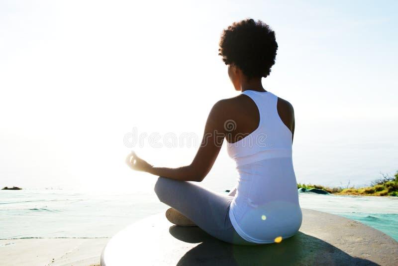 De jonge vrouwenzitting bij strand in yoga stelt stock foto