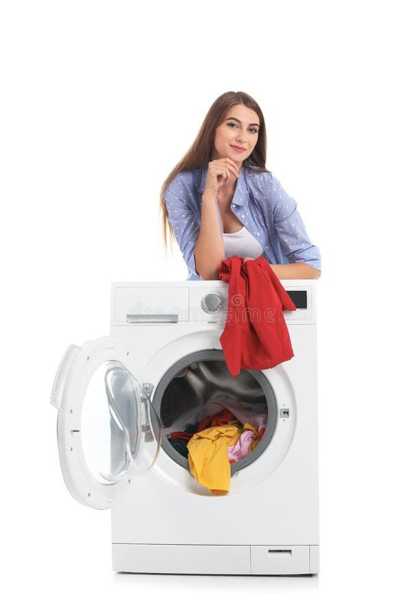 De jonge wasmachine van de vrouwenlading met vuile wasserij stock afbeelding