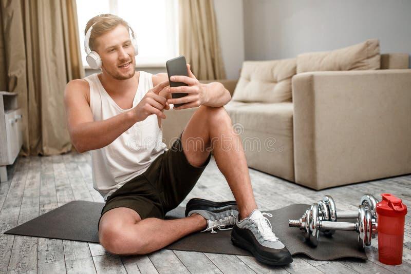 De jonge well-built mens gaat binnen voor sporten in flat De gelukkige positieve kerel zit op carimate op vloer en neemt selfie royalty-vrije stock foto's