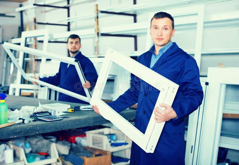 De jonge werklieden inspecteren pvc-productieoutput stock foto