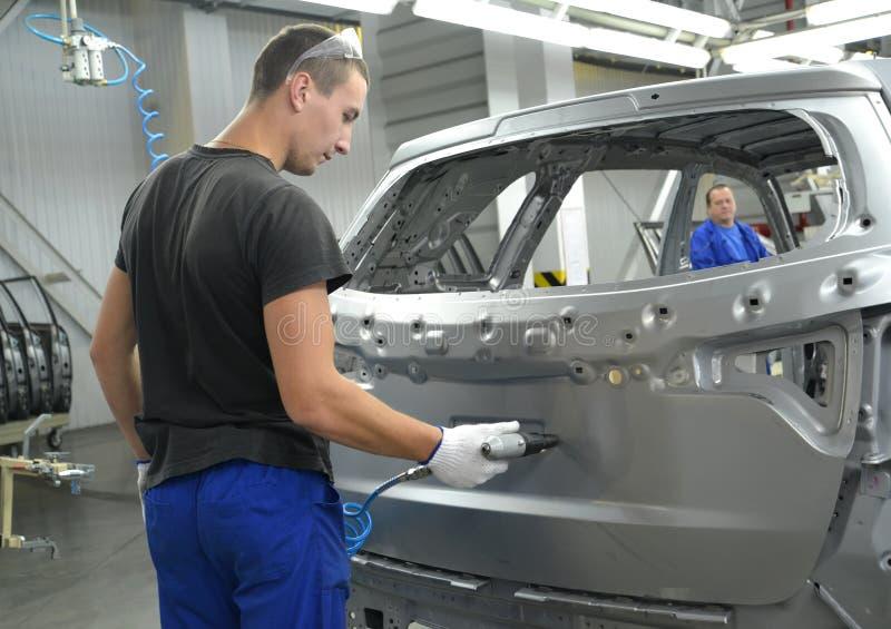 De jonge werknemer boort het openen in een autolichaam een pneumodrill stock foto