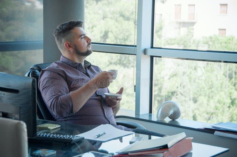 De jonge werknemer in de bureau het drinken koffie, hebt onderbrekingstijd a royalty-vrije stock afbeelding