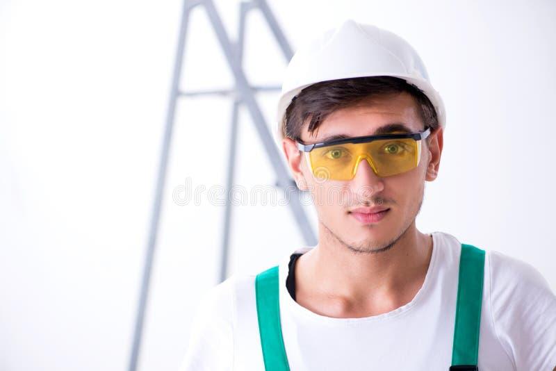 De jonge werknemer met beschermingsmiddel in veiligheidsconcept stock afbeelding