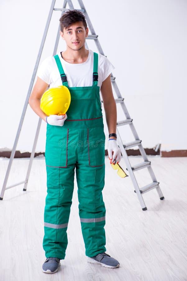 De jonge werknemer met beschermingsmiddel in veiligheidsconcept stock fotografie